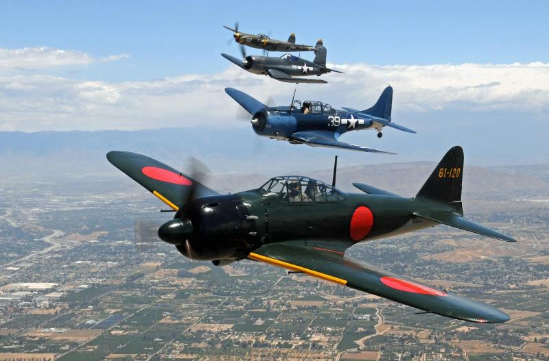 同じく雁行で編隊飛行するゼロ戦52型。2機目はSBD-5ドーントレス。